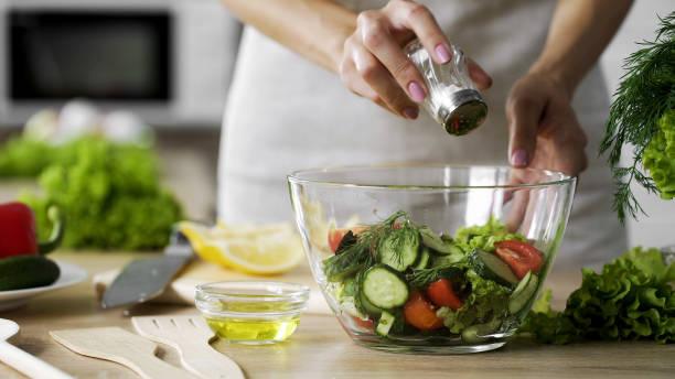 frau, die zugabe von salz in gemüsesalat glasschüssel, gesundheitswesen, übermäßiges salzen - speisesalz stock-fotos und bilder