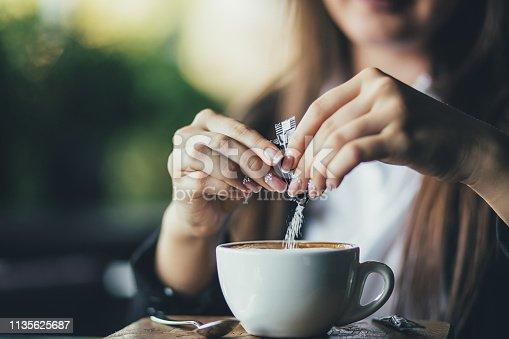 Woman adding sugar to fresh aromatic coffee on table, closeup.