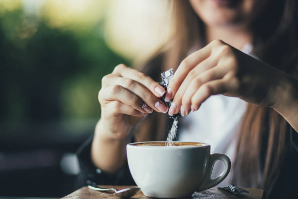 woman adding sugar to fresh aromatic coffee on table, closeup - sweeteners stock photos and pictures