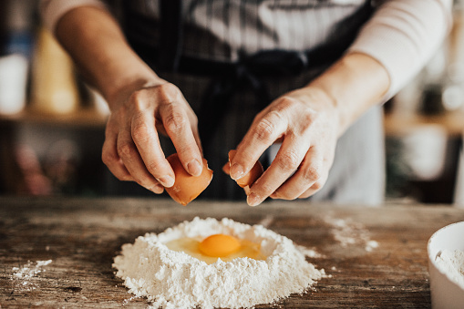 Woman adds an egg to the flour
