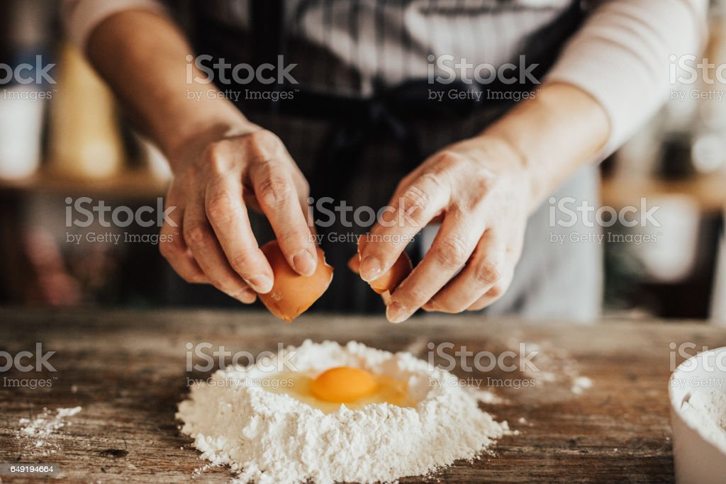 Woman adds an egg to the flour stock photo