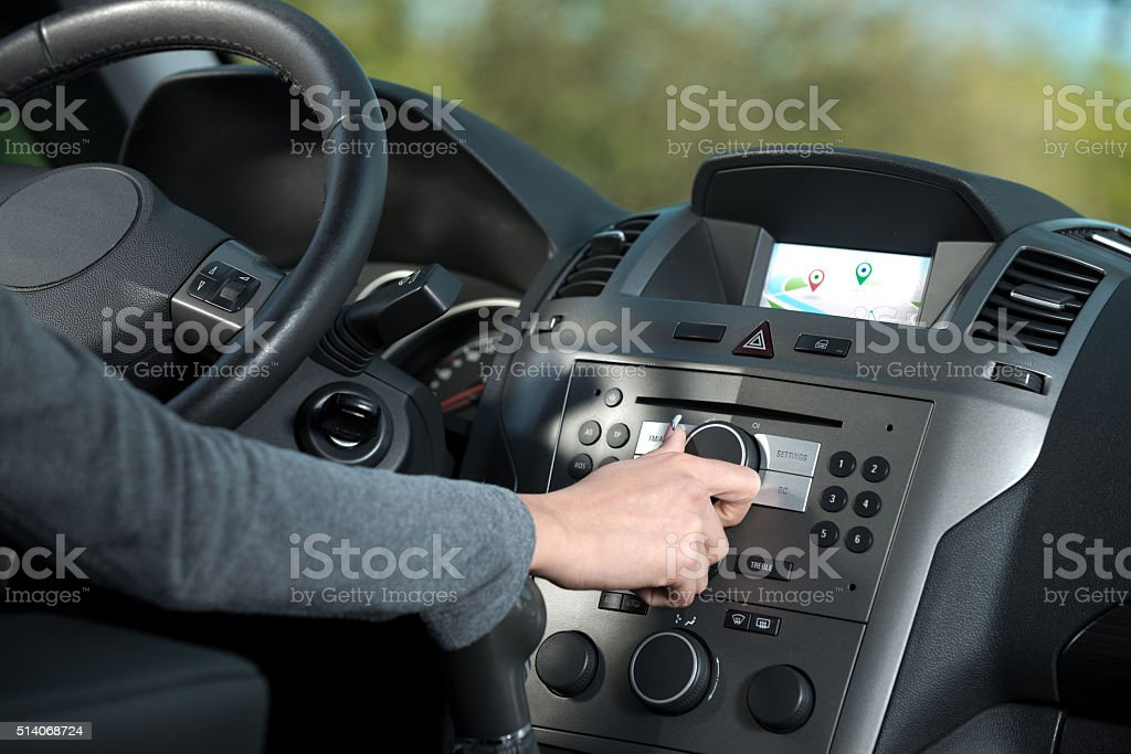 Woman adjusting a knob in her car stock photo