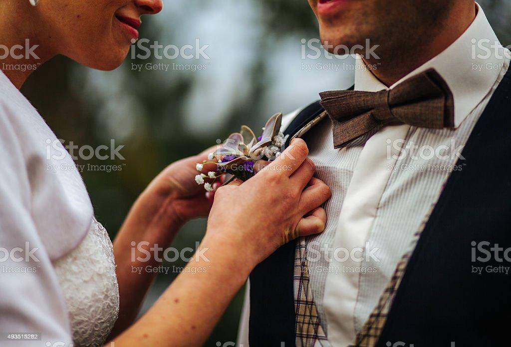 woman adjusting boutonniere stock photo
