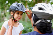 istock Woman adjusting helmet of a little girl smiling 462870655