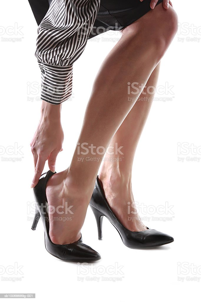 Woman adjusting high heels, close-up, low section royalty free stockfoto