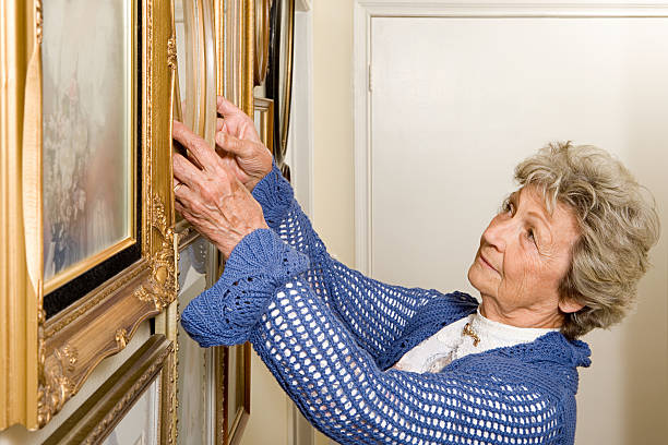 woman adjusting picture frames - curator stock pictures, royalty-free photos & images