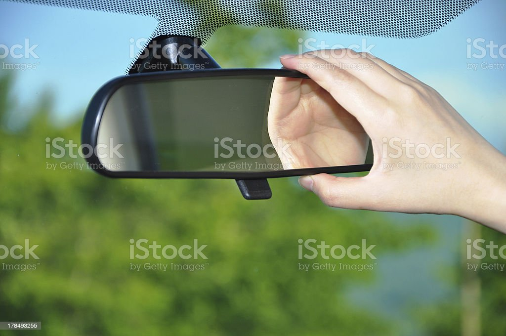 Woman Adjusting Rearview Mirror stock photo