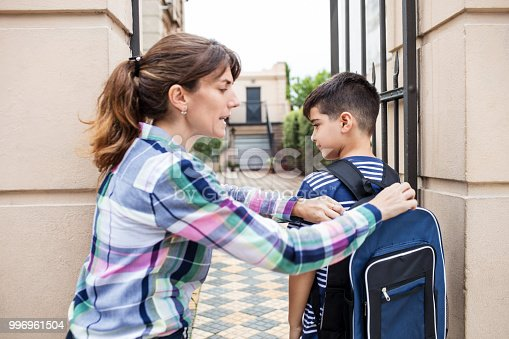 istock Woman adjusting son's backpack at school entrance 996961504