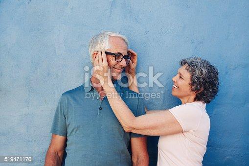 istock Woman adjusting the eyeglasses on her husband 519471170