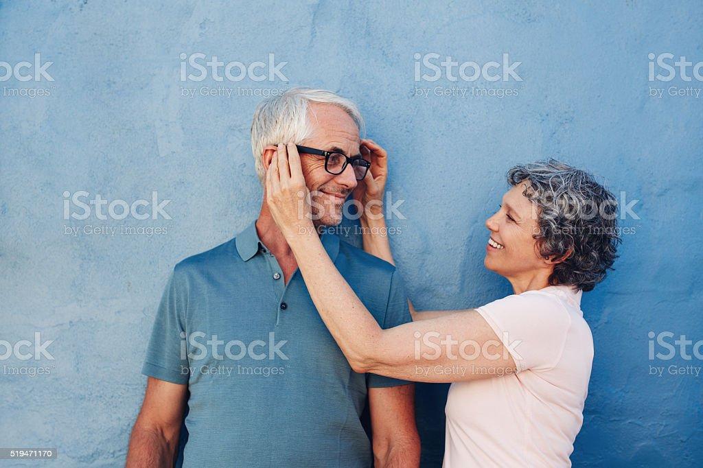 Woman adjusting the eyeglasses on her husband stock photo