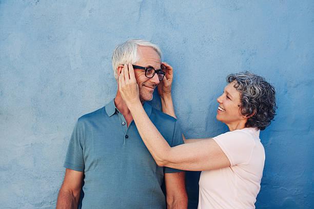 mulher ajustar os óculos em seu marido - lifestyle color background - fotografias e filmes do acervo