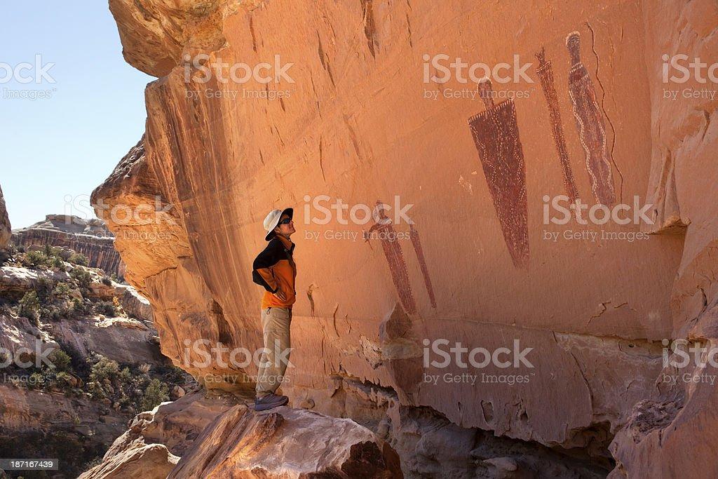 Woman admires Glen Canyon pictographs Utah royalty-free stock photo