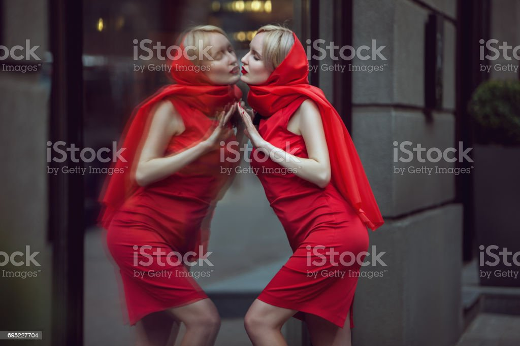 Woman admires herself in reflection. stock photo