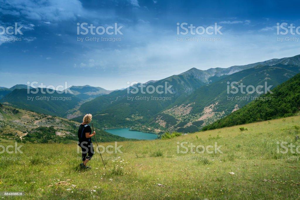 Woman admires lake view in Italian mountains stock photo