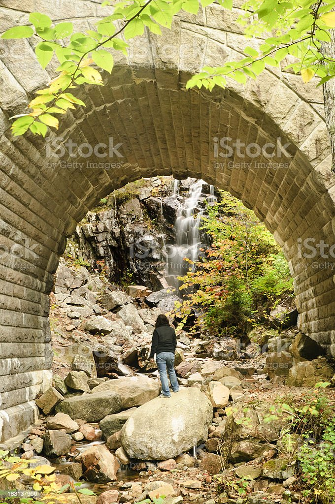 Woman admiring a waterfall. stock photo