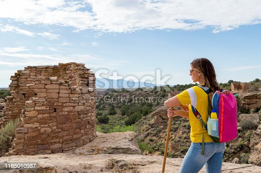 This is a view of a woman hiker admiring some of the Native American (Anasazi) ruins found at Hovenweep National Monument.  This shot was taken from the top of the Mesa that surrounds the Square Tower Group.  Featured in this shot is a structure called Tower Point.