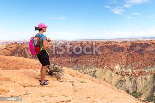 This photo shows a woman admiring the view from the top of the crater on the edge of Upheaval Dome in Canyonlands National Park, Utah, USA.