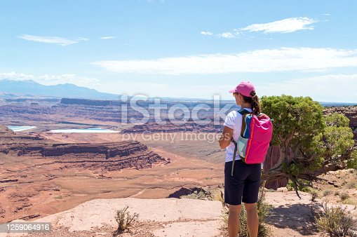 This photo shows a woman admiring the view from the top of the mesa in Dead Horse Point State Park in Utah.  Visible are rock spires and eroded canyon features below.  In the distance are white and blue evaporation ponds.  These ponds produce potash or potassium chloride salt.