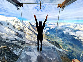 istock Woman admiring the view from the Glass box, the Step into the Void - Aiguille du Midi Skywalk 1278571201