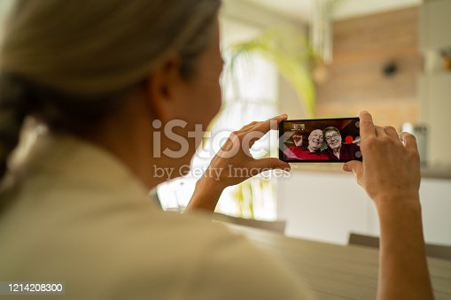 over the shoulder view mature adult woman talking with her smiling waving senior parents via mobile phone video telephony during corona quarantine in living room of house in times of social distancing to stay safe and healthy