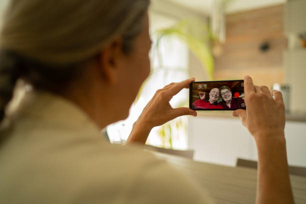woman adult daughter connected with her senior parents through mobile phone video call during coronavirus crisis - social distancing stock pictures, royalty-free photos & images