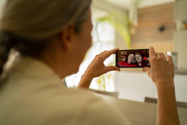 woman adult daughter connected with her senior parents through mobile phone video call during coronavirus crisis - prevenzione delle malattie foto e immagini stock
