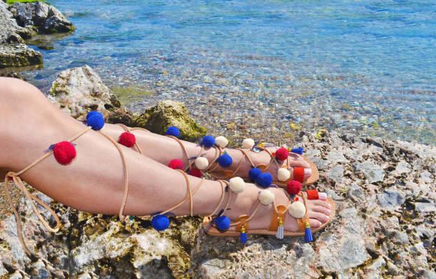 woman advertises traditional greek sandals gladiator on beach stock photo