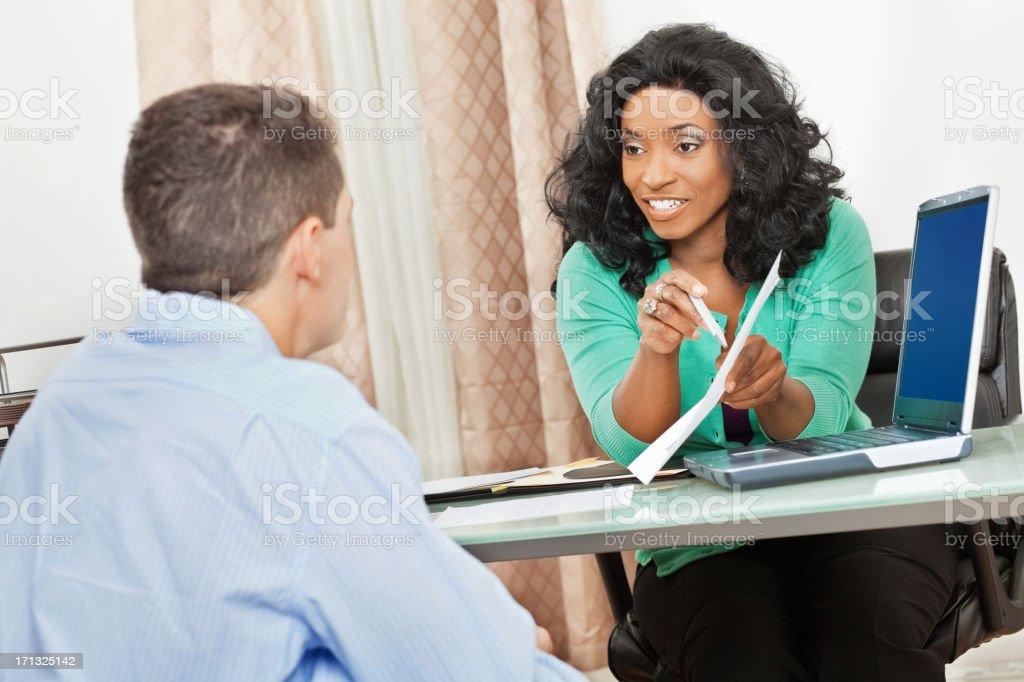 Woman advising man using charts and computer stock photo