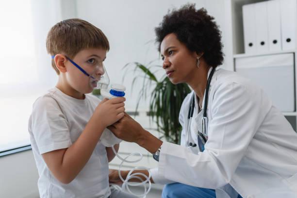 kvinna afroamerikansk läkare allmänläkare hjälpa barn att sätta nebulizer inhalator ansiktsmask. astmabehandling för barn. - andningssystem bildbanksfoton och bilder