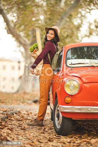 Happy woman after groceries shopping standing near car