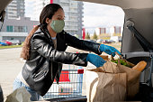 Young woman in mask and gloves putting paper bags into car trunk after supermarket shopping