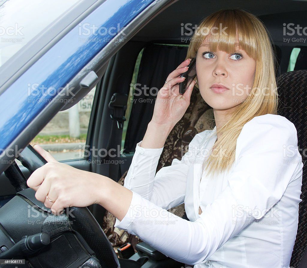 woman after the helm of car with a telephone stock photo