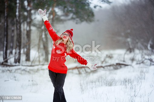 A woman against a snowy valley dressed in mittens and a red sweater.