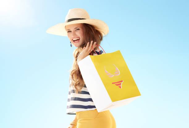 Frau gegen blauen Himmel mit gelben Einkaufstasche mit bikini – Foto
