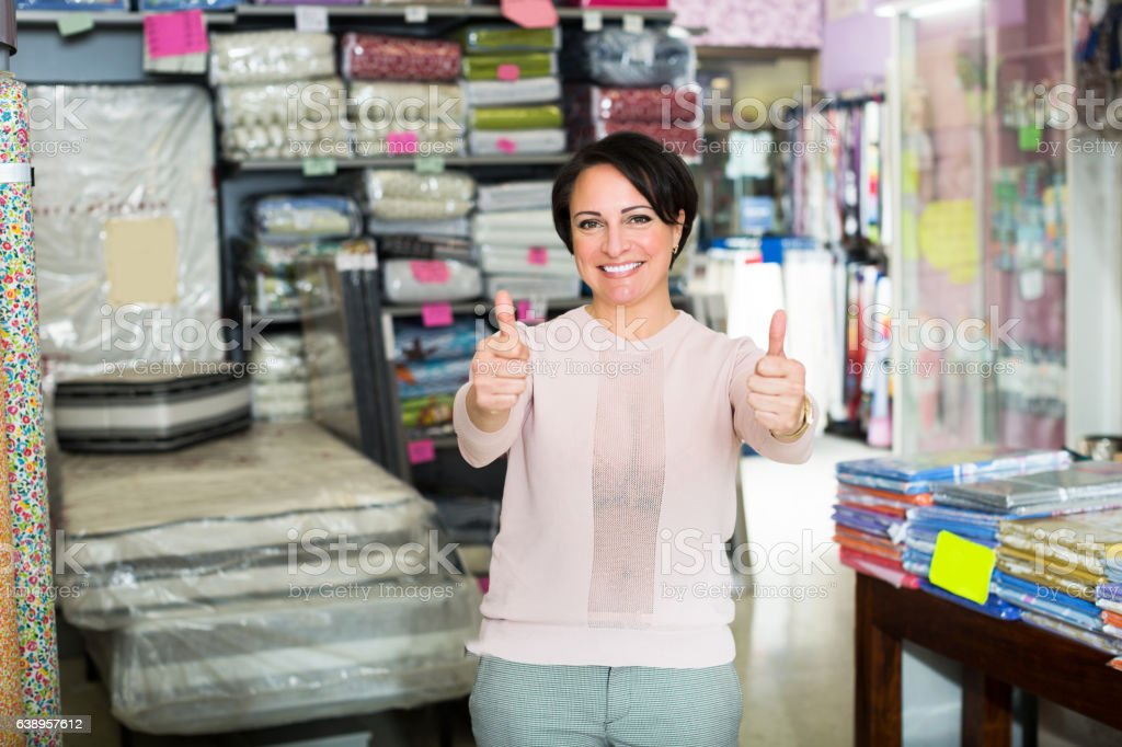 Woman against interior of textile store stock photo