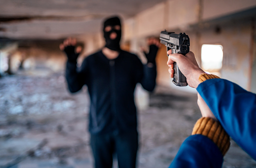 Caucasian man in black with mask with his hands up while a caucasian woman point at him with a hand gun