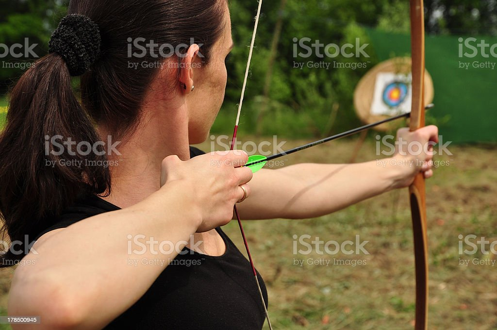 Woman aiming her bow and arrow at a target stock photo