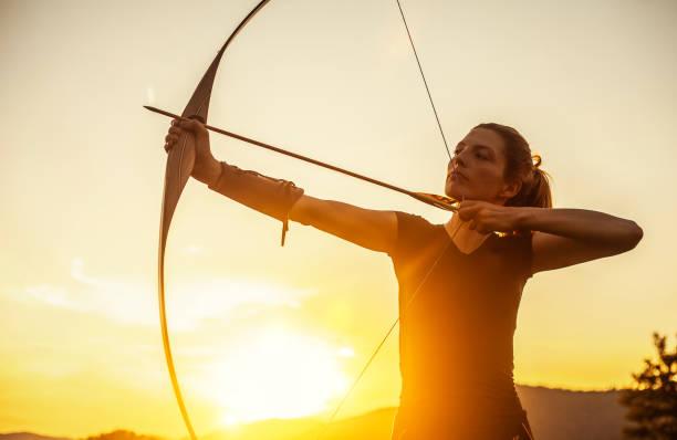 femme visant dans le tir à l'arc - tir à l'arc photos et images de collection