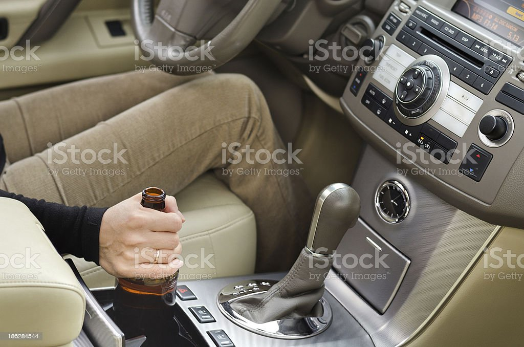 Woman alcoholic with a bottle of booze in the car stock photo