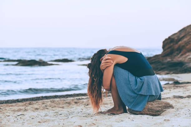 frau allein und deprimiert sitzen am strand - bedauern stock-fotos und bilder