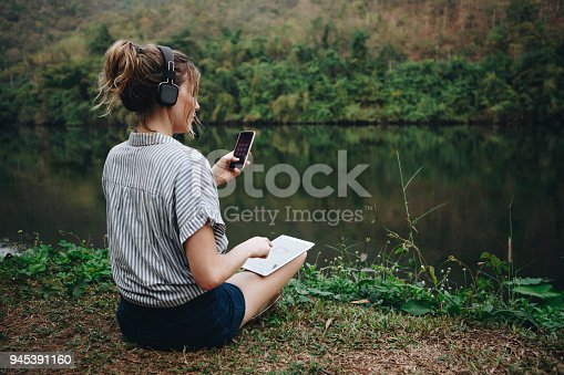 Woman alone in nature listening to music with headphones, digital tablet and a smartphone music and relaxation concept