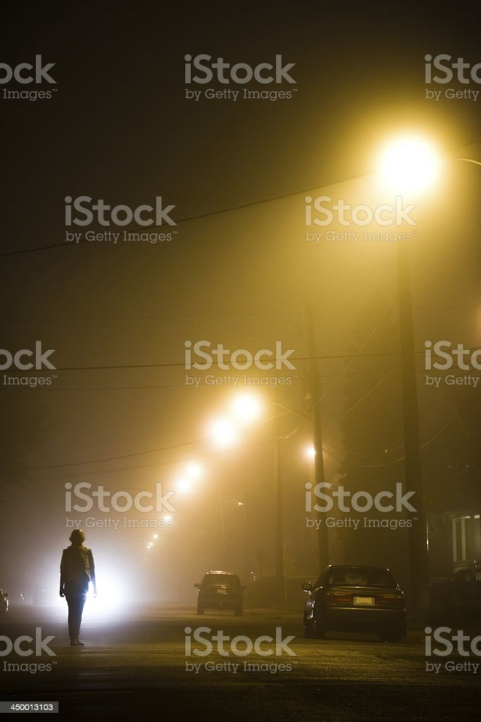 Woman alone in the foggy street stock photo