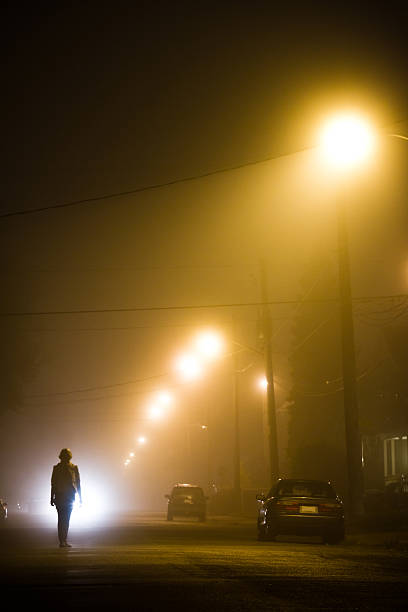 woman alone in the foggy street - mist donker auto stockfoto's en -beelden