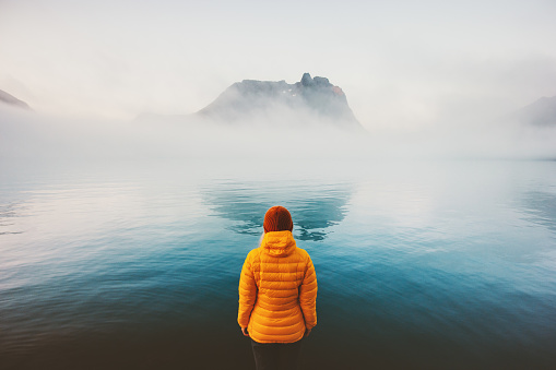 Woman alone looking at foggy sea traveling adventure lifestyle outdoor solitude sad emotions winter down jacket clothing cold scandinavian minimal landscape