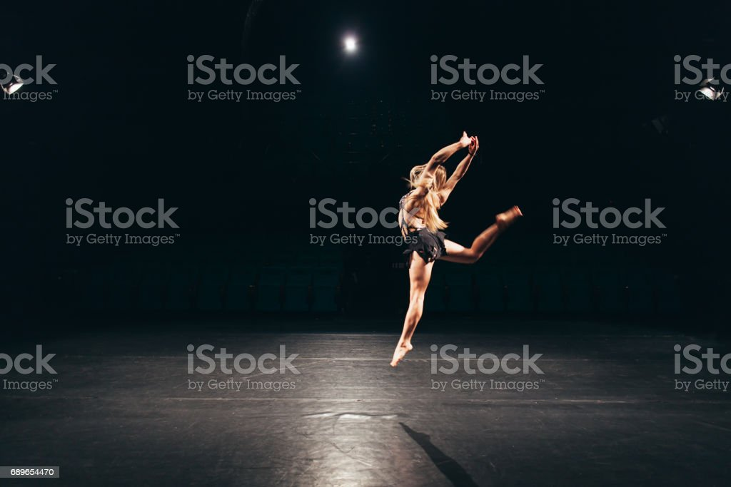 woman alone on stage doing modern dance performance stock photo