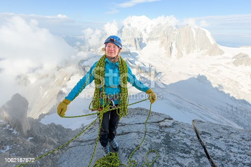 Woman alpinist coiling her rope on a rock ledge in front of Mont Blanc in the Alps