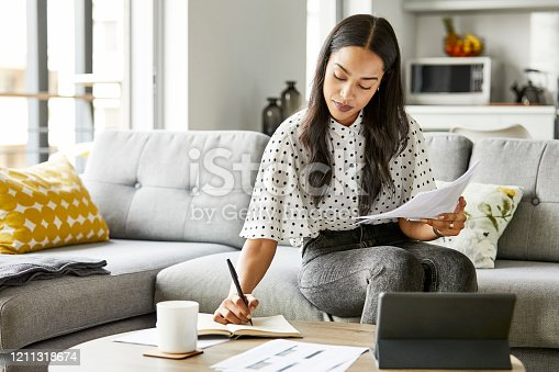 Woman analyzing bills while writing in diary. Female is using digital tablet at table. She is sitting on sofa at home.