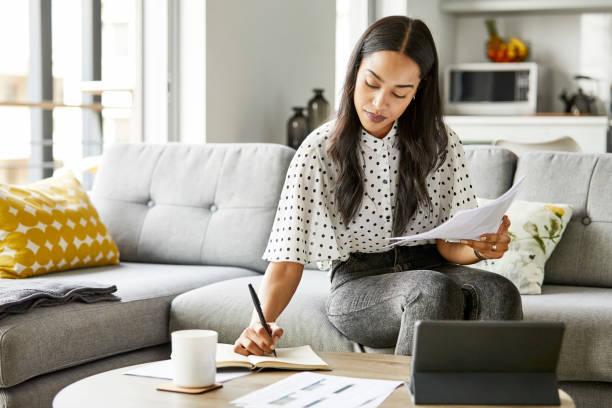 Frau analysiert Rechnungen, während sie zu Hause sitzt – Foto