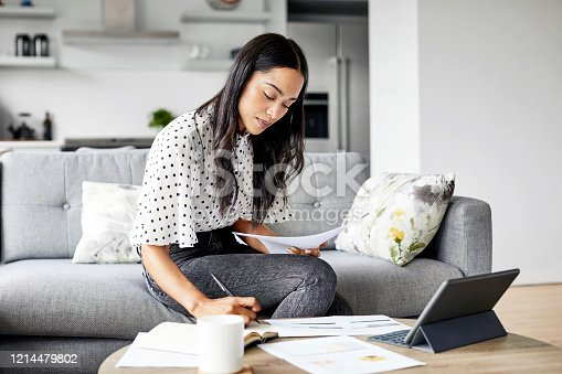 Young woman analyzing bills while writing in diary. Beautiful female is using digital tablet at table. She is sitting on sofa at home.