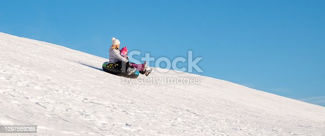 istock A woman and a child, 5 years old, Caucasians, quickly ride down a snow-covered slide on an inflatable ring. 1297559265